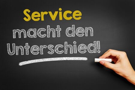 macht: Hand writes in German Service macht den Unterschied! (Service makes the difference!) on blackboard Stock Photo