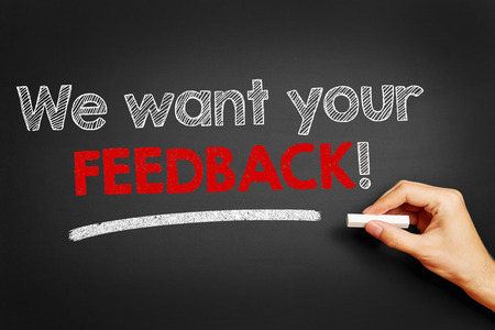 important information: Hand writes We want your feedback! on blackboard Stock Photo