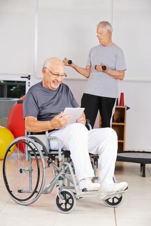 terapia ocupacional: Hombre mayor en silla de ruedas con la lectura del ebook tablet PC en un hogar de ancianos Foto de archivo