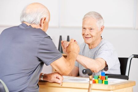 eldercare: Two old senior men holding hands for congratulation in a nursing home