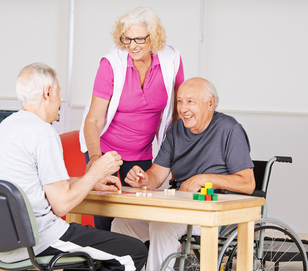an elderly person: Happy senior people playing Bingo together in a nursing home Stock Photo