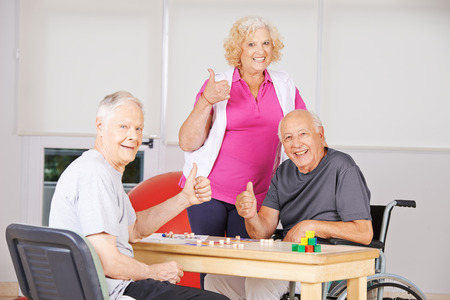 Three happy senior people in nursing home holding thumbs up and playing Bingo photo