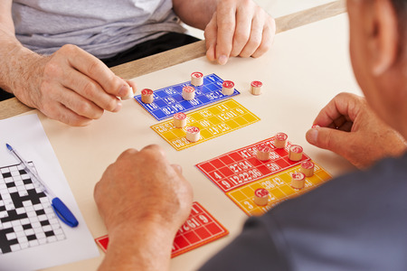 retirement age: Old men playing Bingo together in a nursing home