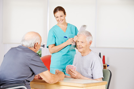 care allowance: Two old men playing cards in a nursing home with smiling nurse watching
