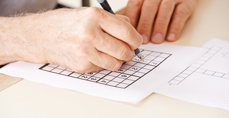 eldercare: Hand of senior man solving sudoku quiz with a pen Stock Photo