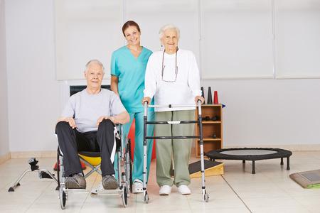fisioterapia: Dos personas mayores con la enfermera durante la fisioterapia en un hogar de ancianos