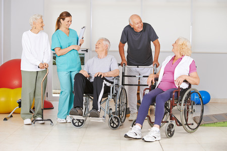 old home: Group of senior people with and without disabilities with geriatric nurse at physiotherapy Stock Photo