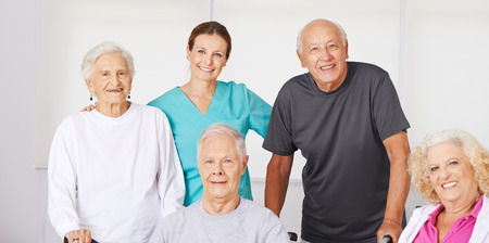 Happy group of senior citizens in nursing home with geriatric nurse Stock Photo