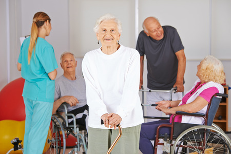 Smiling old woman standing in front of group of senior people in nursing home photo