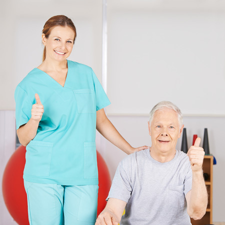 mobility nursing: Physiotherapist and patient holding thumbs up in a nursing home Stock Photo