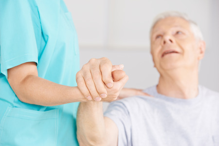 senior citizen woman: Nursing assistant holding hand of senior man for support Stock Photo