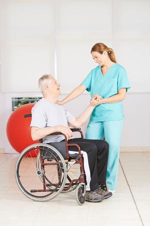 terapia ocupacional: Viejo hombre en silla de ruedas en la fisioterapia en un hogar de ancianos Foto de archivo