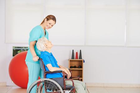 fisioterapia: Dring Cuidador mujer mayor en silla de ruedas a la fisioterapia Foto de archivo