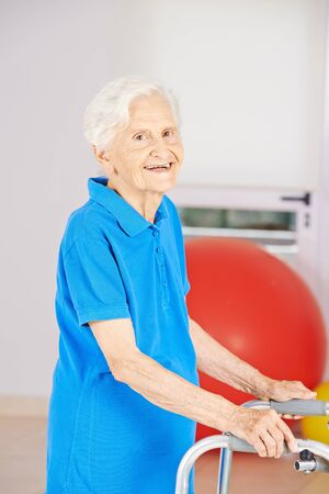 mobility nursing: Old smiling senior woman going with walker to physiotherapy Stock Photo