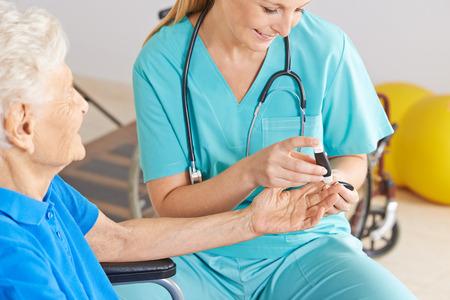 Geratric verpleegkundige controle bloedsuikerspiegel van senior vrouw met diabetes