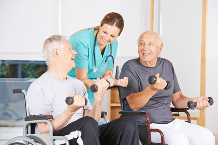 rehab: Two senior men in wheelchairs lifting dumbbells during physiotherapy