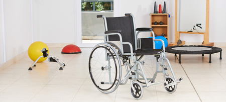 silla de rueda: Sill�n de ruedas vac�o de pie como s�mbolo de la fisioterapia en la sala de gimnasio Foto de archivo