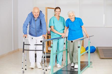 Twee senior mensen doen looptraining in de fysiotherapie met fysiotherapeut Stockfoto