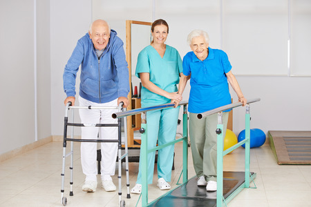 senior health: Two senior people doing walking exercise in physiotherapy with physiotherapist