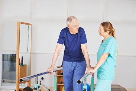 Oude man bij fysiotherapie op een loopband met fysiotherapeut