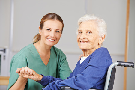 Les soins gériatriques avec l'infirmière et de femme âgée heureuse dans un fauteuil roulant Banque d'images