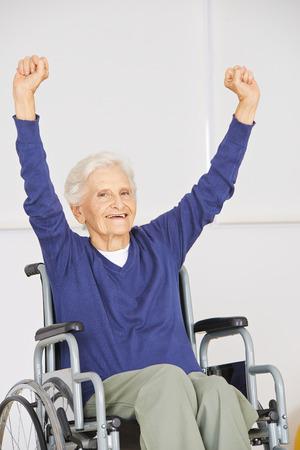 Vieja mujer mayor en silla de ruedas que anima con los brazos arriba Foto de archivo