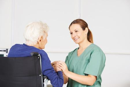 hospitales: La mujer mayor en una silla de ruedas como paciente con la enfermera geriátrica en un hogar de ancianos