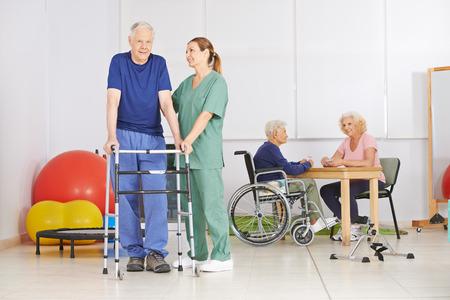 vejez feliz: Viejo hombre con andador durante pyhsiotherapy en un hogar de ancianos