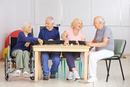 discapacitados: Feliz grupo de personas mayores que juegan al juego rummy en un hogar de ancianos