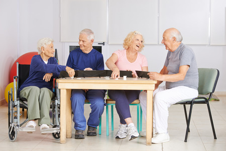 Happy group of senior people playing rummy game in a nursing home