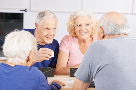 old people group: Group of senior people playing rummikub game in a nursing home Stock Photo