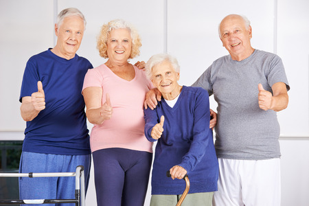 Happy group of seniors holding thumbs up in a nursing home