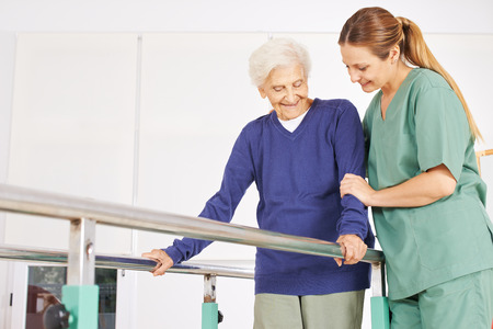 Physiotherapist helping old senior woman on treadmill with handles Foto de archivo