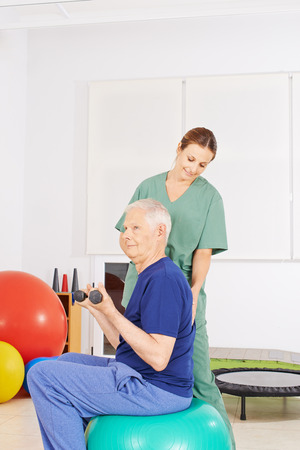 physical: Old man with dumbbells on gym ball in a physical therapy praxis