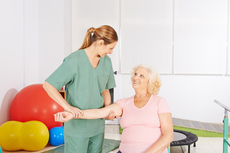 occupational therapy: Old woman with aching shoulder in physical therapy doing exercises Stock Photo