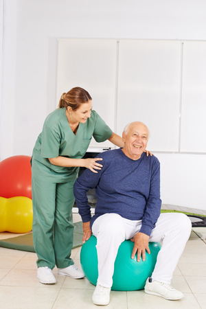 Senior man with aching back sitting in physical therapy on a gym ball Stock Photo