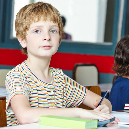 left handed: Smiling child in class in elementary school and writing lefthanded