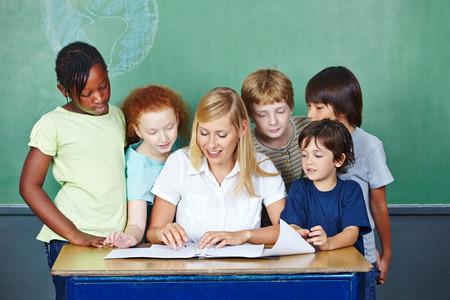 grading: Profesor que explica la clasificaci�n de los estudiantes de primaria en su escritorio