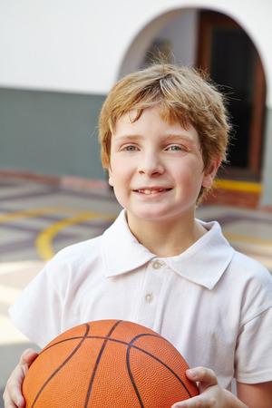 educacion fisica: Ni�o con el baloncesto en la clase de educaci�n f�sica en la escuela Foto de archivo
