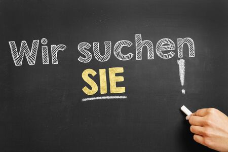 sought: Hand writes in German Wir suchen SIE! (We ware looking your YOU!) on blackboard Stock Photo
