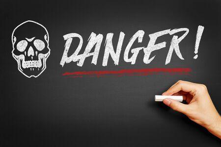mortal danger: Hand with chalk writing Danger! on a blackboard