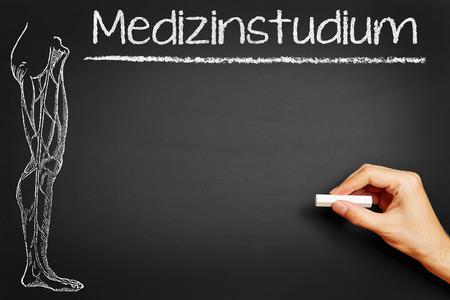 medical school: Hand writing the German word Medizinstudium (medical school) on a blackboard Stock Photo