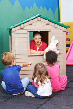 Nursery teacher using playhouse for theater play with stuffed animals for children Foto de archivo