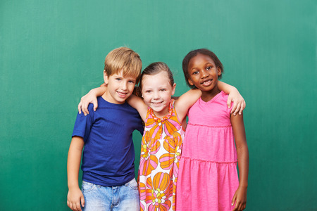 kids hugging: Three happy friends embracing in kindergarten in front of a green wall Stock Photo