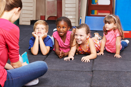 Nursery teacher reading story book to group of kids in kindergarten Foto de archivo