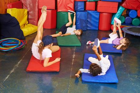 Groep kinderen oefenen in de lichamelijke opvoeding in voorschoolse Stockfoto