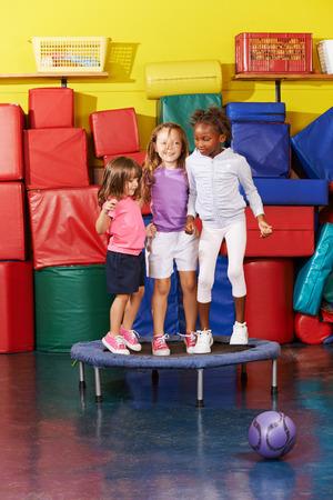 Tres niños saltando en el trampolín juntos en el gimnasio de un jardín de infantes