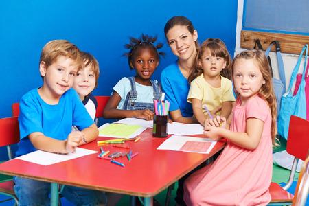 Grupo de niños que pintan en la mesa con el maestro de cuarto de niños en un jardín de infantes