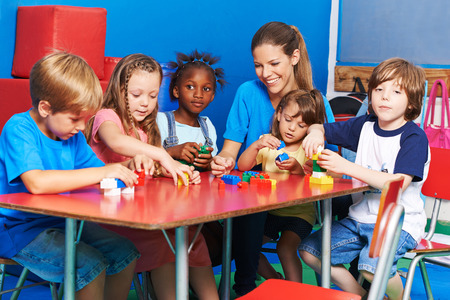 blocks: Children and nursery teacher playing with building blocks in a kindergarten
