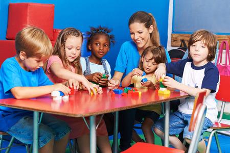 kinder: Niños y profesor vivero jugando con bloques de construcción de un jardín de infantes Foto de archivo